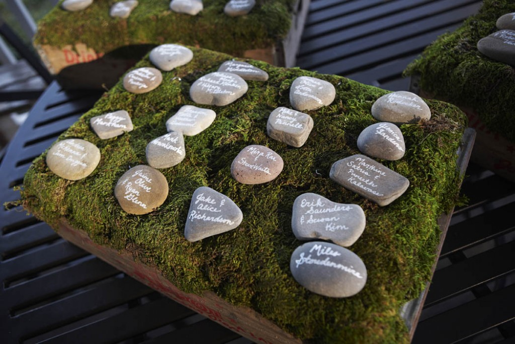 "Escort ""cards"" -river rocks with guest's names & table numbers on a bed of moss."